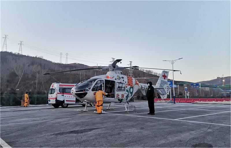 张家口赛区相约北京冬季体育系列测试活动期间,棋盘梁临时交通场站红十字紧急救援直升机停机坪火速建成。图为场站工作人员和红十字会直升机地勤人员指挥直升机停放。 张家口市交投集团供图