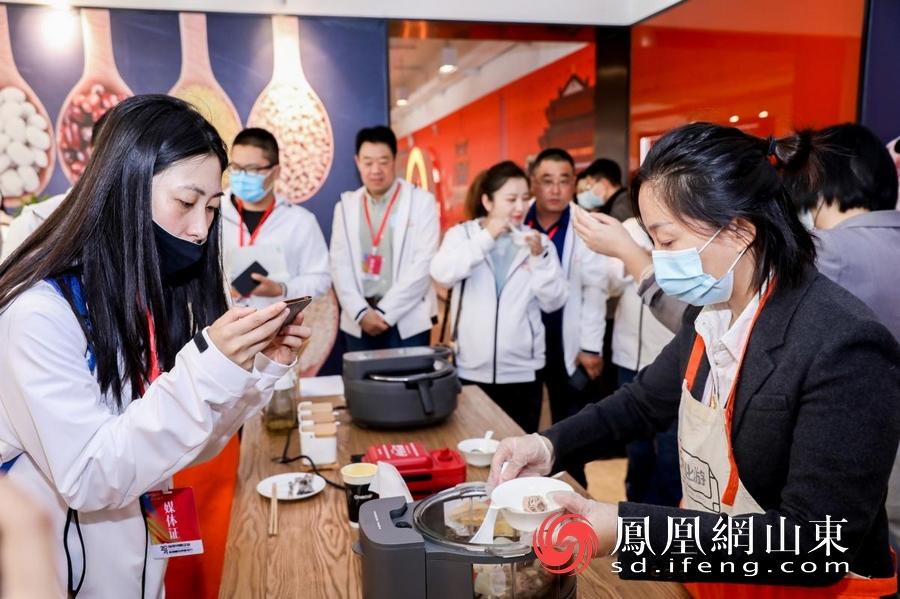 媒体记者品尝九阳无涂层蒸汽饭煲S160蒸制的无水鸡汤。