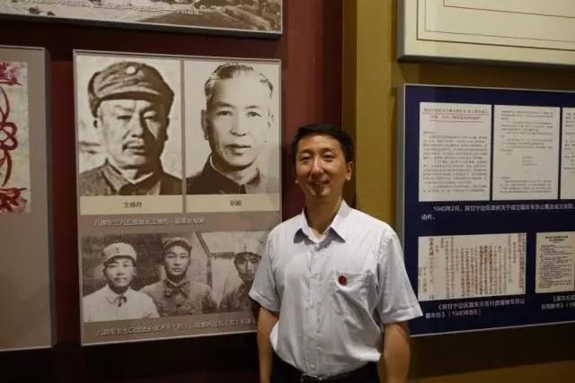 (2015年,耿巍在庆阳南梁革命纪念馆有关爷爷的展板前留影。)
