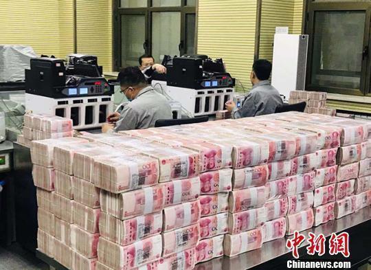 银行的点钞员在清点人民币。(资料图) 艾庆龙 摄<br>