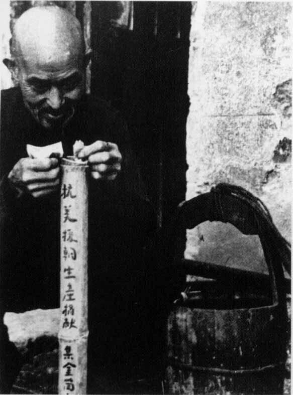 (湘潭70多岁老人谭楚云把卖水的钱存入竹筒,为购买武器作贡献。资料图片)