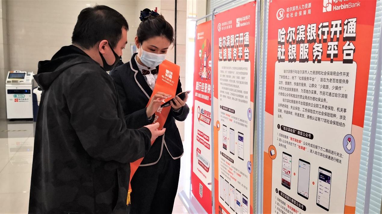 """图为哈尔滨银行工作人员帮助客户通过""""社银服务平台""""办理业务。"""