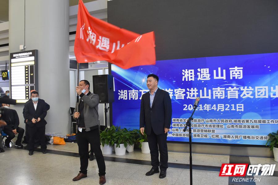 """为2021""""湖南万名游客进山南""""首发团代表授旗。"""