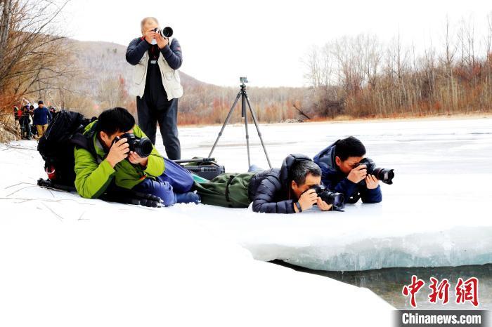 摄影爱好者趴着拍摄冰河。 冯宏伟 摄