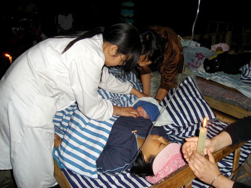 震后一天,医生为产妇做母乳喂养的指导,产妇的母亲则在床头手持着蜡烛为其照明。翟秋榕 摄