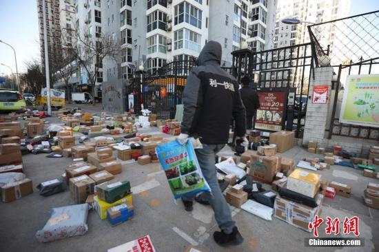 """3月3日,北京朝阳区一小区门口,快递员为居民查找搬运快递物品。受疫情影响,许多市民""""宅""""在家中,网购成为消费主流,而线上下单量也随之呈现爆发式增长,不少小区门口出现快递物品扎堆的现象。<a target='_blank' href='http://www.chinanews.com/'>中新社</a>记者 赵隽 摄"""