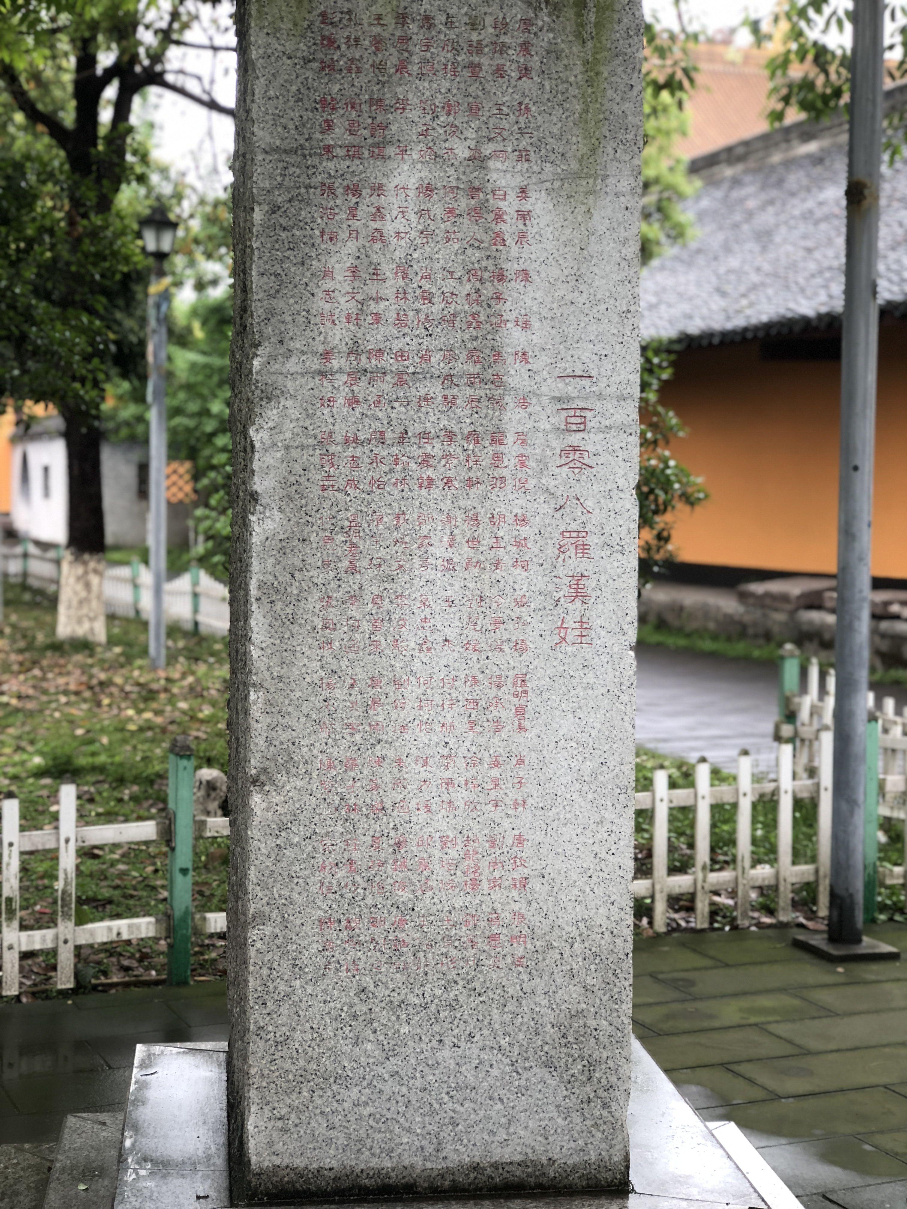 """罗汉寺放生池畔的""""一百零八罗汉娃""""纪念碑。新京报记者 吴淋姝 摄"""