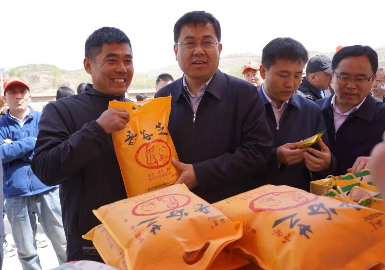 图为娄烦县委书记李树忠在活动现场了解特色农产品