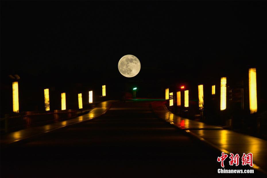 4月27日夜,一轮超级圆月现身甘肃古郡敦煌夜空。图为在鸣沙山月牙泉景区观赏大漠圆月。(多重曝光)中新社发 王斌银 摄