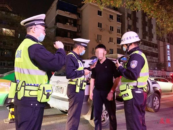 ▲南昌市公安交管局西湖大队一中队的民警正对一名疑似酒驾的驾驶员进行检查。