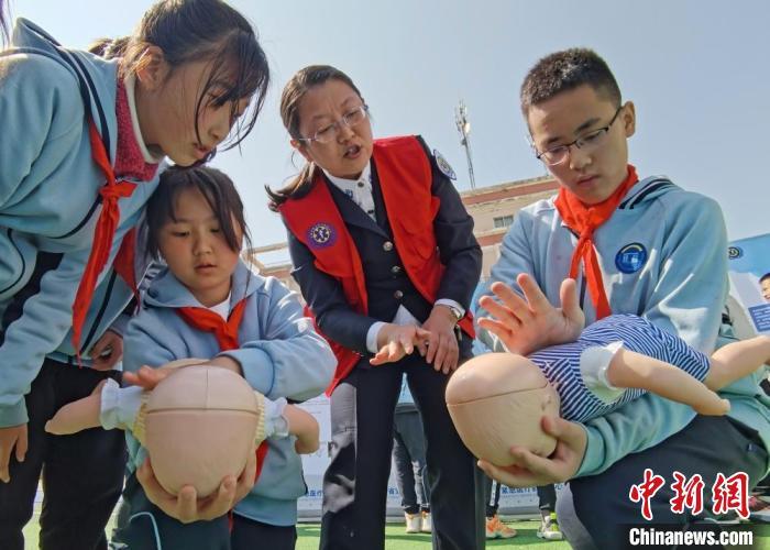 图为兰州市小学生在救援中心专业人员指导下练习急救技能。 闫姣 摄