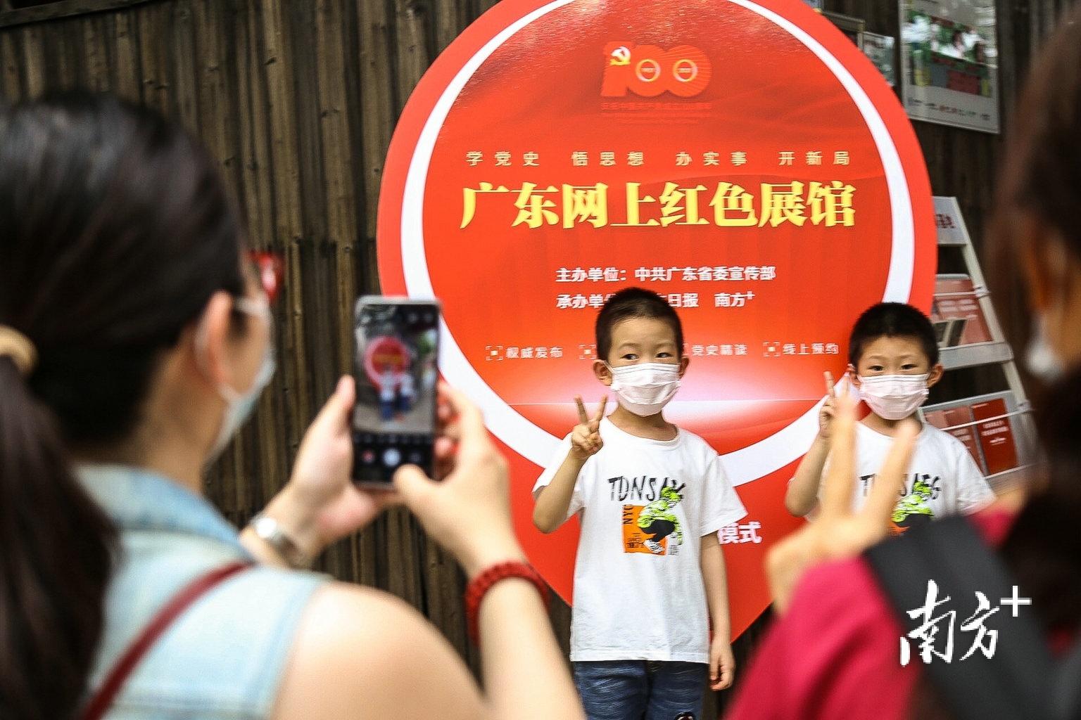 """""""五一""""假期,不少家长带着孩子前往毛泽东同志主办农民运动讲习所旧址纪念馆游览参观。图为孩子在广东网上红色展馆拍照板前合影留念。南方日报记者 张迪 实习生 姚佳烁 摄"""