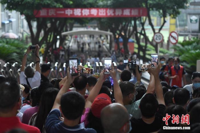 资料图:2020年7月7日,重庆市第一中学校考点,家长迎接孩子。中新社记者 陈超 摄