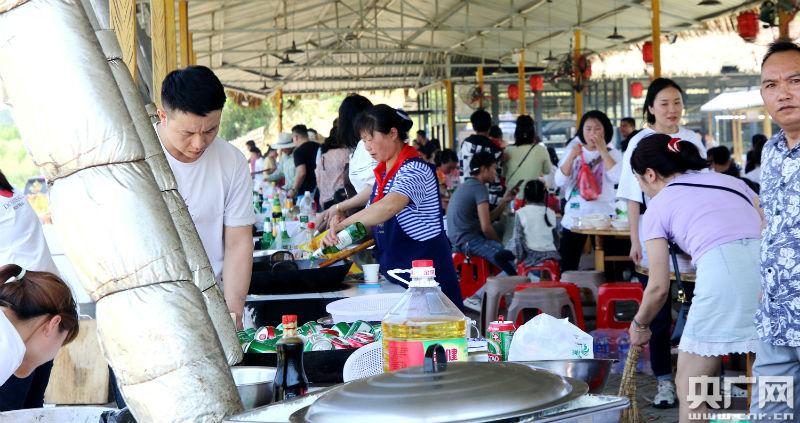 游客们体验烧柴火灶,吃大锅菜项目(央广网发 通讯员提供)