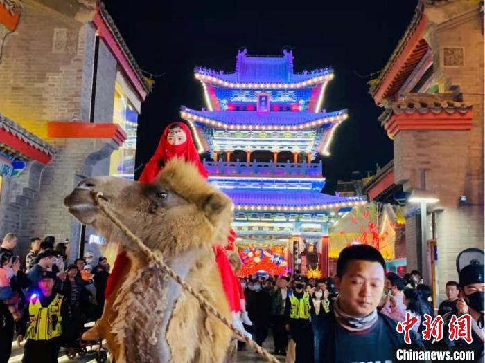 """图为驼队与人群""""再现""""古丝绸之路繁荣盛况,引得市民和游客客""""梦回""""千年以前。 刘芯羽 摄"""