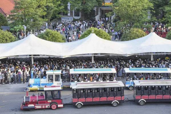 (5月1日,长沙市橘子洲景区,等待乘坐观光车的市民和游客排起长队。湖南日报·新湖南客户端 记者 辜鹏博 摄)