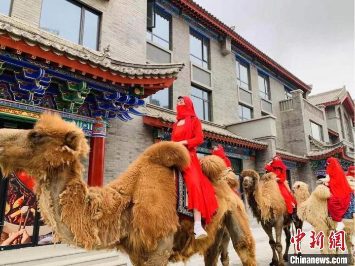 """图为演员装扮成异域女子,骑行骆驼""""巡游""""位于七里河区的兰州老街。 闫姣 摄"""