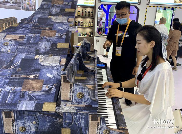李女士对这架能变身的钢琴很感兴趣。长城网记者 李丽钧 摄