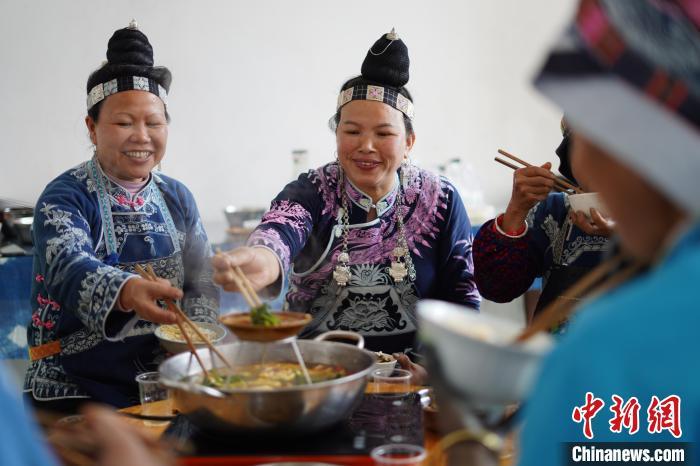 图为杨而报浪(左二)和蜡染画师在蜡染制作车间吃午饭。 杨武魁 摄