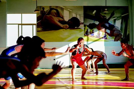 在江西省萍乡市武功山风景名胜区麻田中心学校的摔跤馆,朱志辉(中)给学生示范摔跤动作要领(2020年11月11日摄)。新华社 图