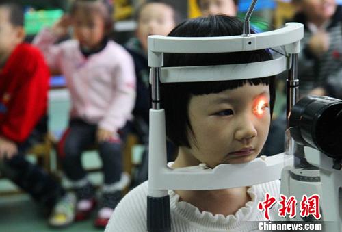 资料图:孩子们在检测视力。中新社发 韩苏原 摄
