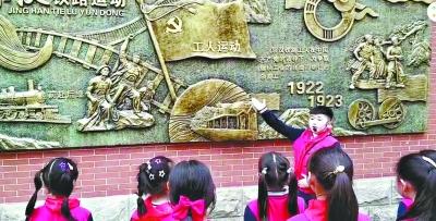 京汉学校门生报告该校铜板浮雕上的汗青。