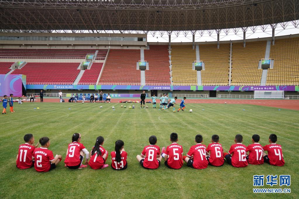 在宝鸡市体育场,陕西省千阳县燕伋小学的12名学生观看宝鸡酷锐青少年足球俱乐部小球员进行攻防练习(5月23日摄)。