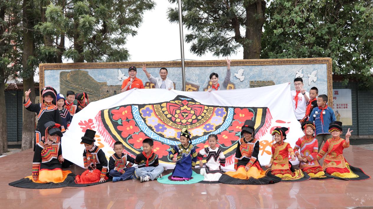 """凤凰网公益专项基金顾问王国祺和孩子们共同展示""""彝族披肩""""绘画作品"""