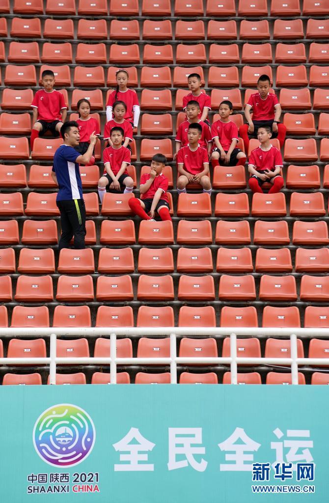 在宝鸡市体育场,宝鸡酷锐青少年足球俱乐部教练吴健(前)为陕西省千阳县燕伋小学的学生讲解足球技战术(5月23日摄)。