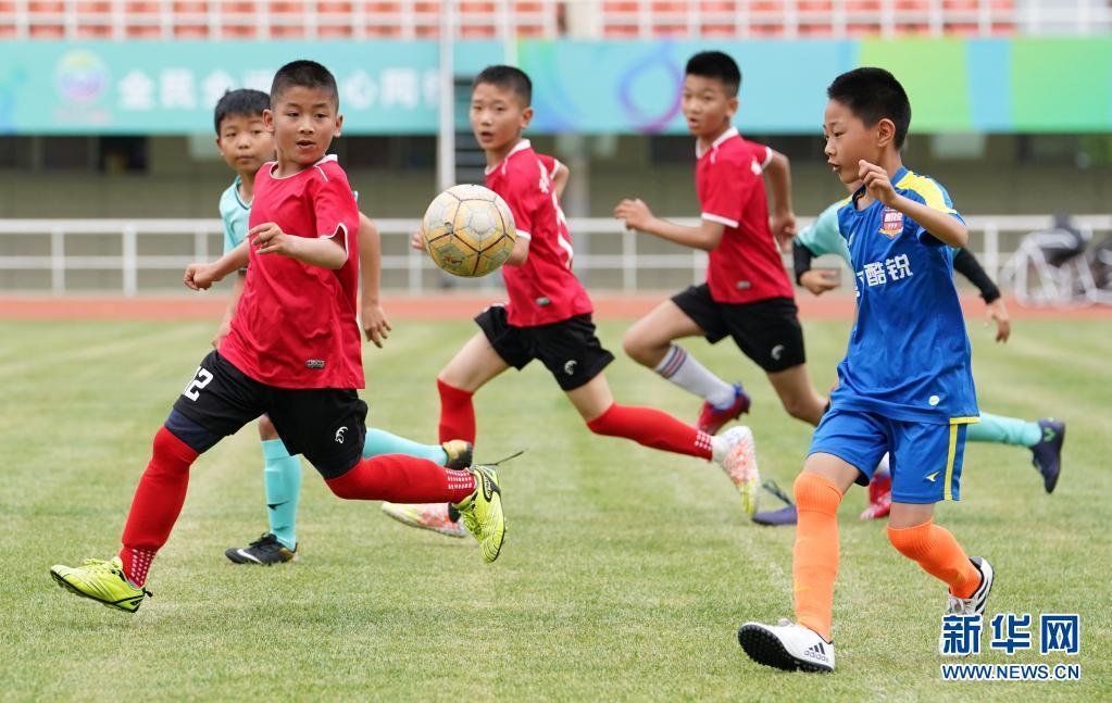 在宝鸡市体育场,陕西省千阳县燕伋小学的学生(前左)与宝鸡酷锐青少年足球俱乐部的小球员切磋球技(5月23日摄)。