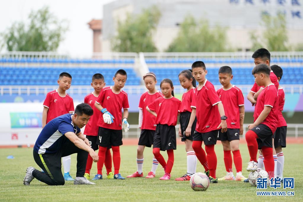 在宝鸡市体育场,宝鸡酷锐青少年足球俱乐部教练吴健(前左)为陕西省千阳县燕伋小学的学生做射门示范(5月23日摄)。