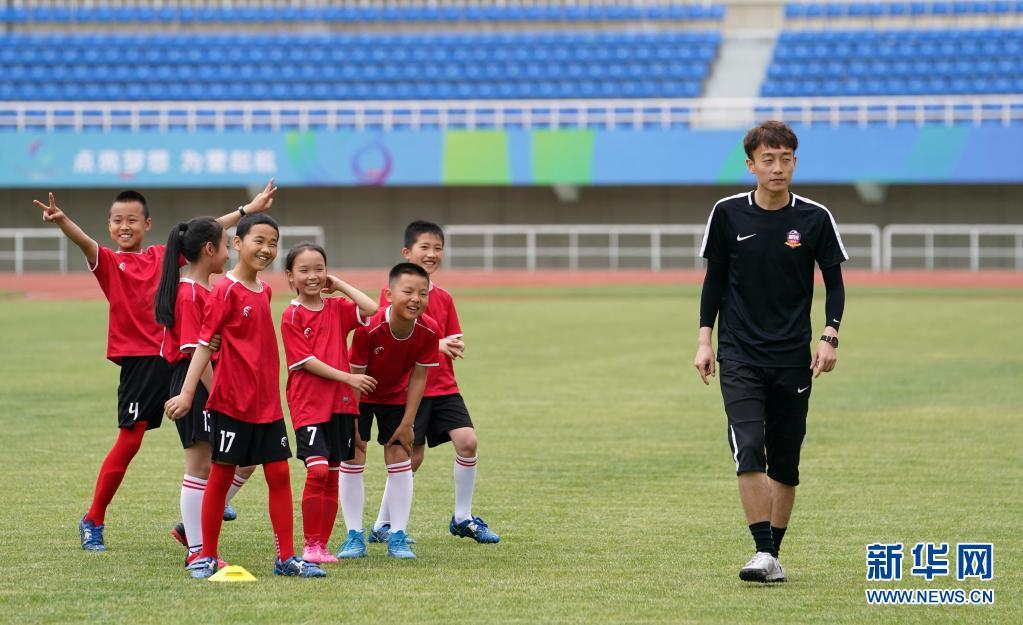 在宝鸡市体育场,宝鸡酷锐青少年足球俱乐部教练胡新宇(右)指导陕西省千阳县燕伋小学的学生训练(5月23日摄)。