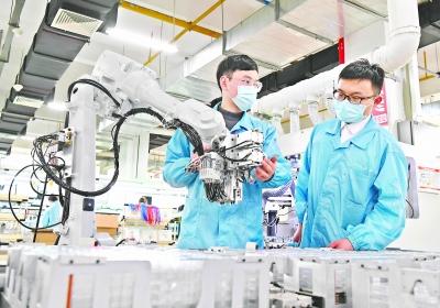 中国信科-中信科移动通信技术有限企业宽敞明亮的智慧工厂生产车间里,工作人员在操作无人生产线。