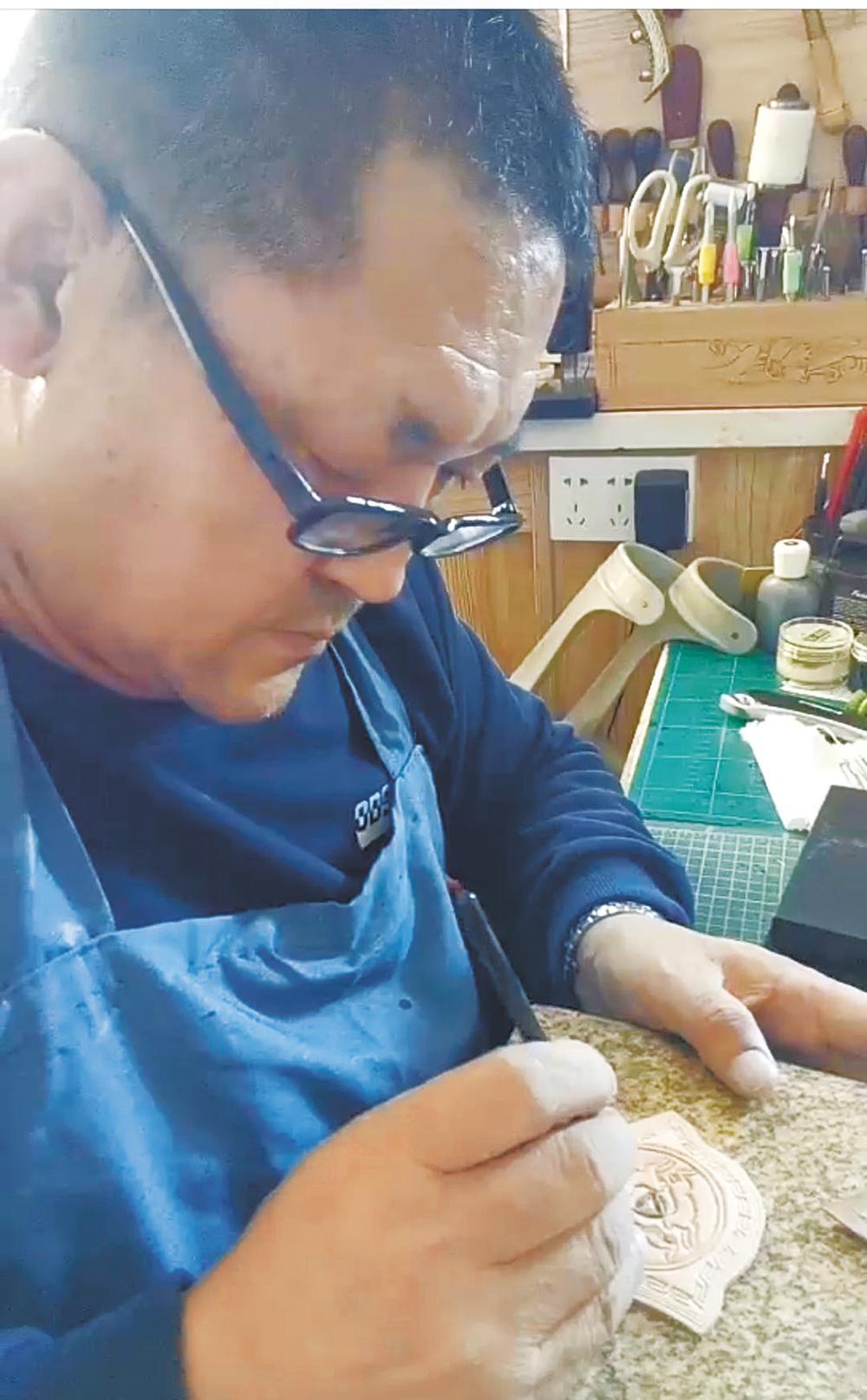 万德在制作传统皮艺压擦图案