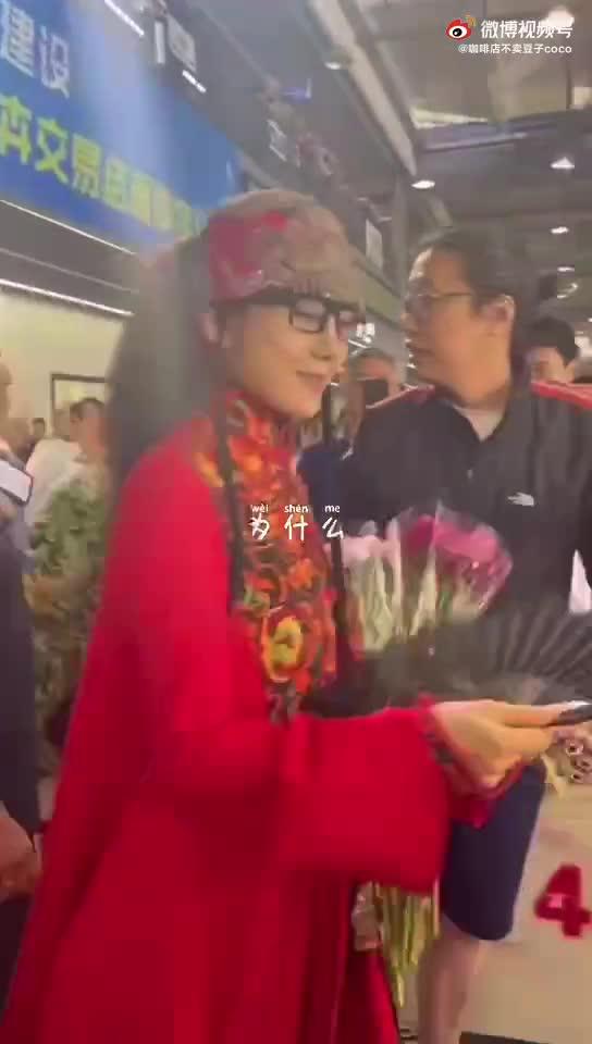 63岁杨丽萍一身红衣逛花市,手拿折扇步伐矫健
