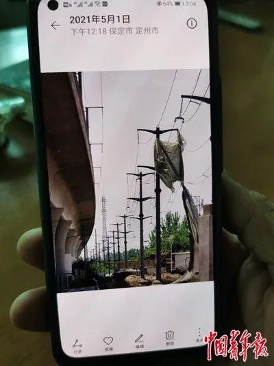 村民用手机拍摄到塑料布挂在供电线上。
