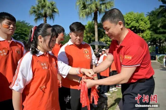 资料图:广西华侨实验高中的教师为高三学子系上红丝带,盼望学子高考必胜。俞靖 摄