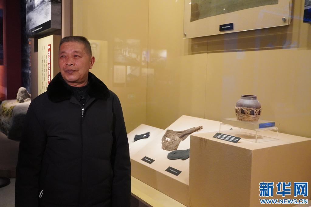 李球德在井冈山革命博物馆介绍他爷爷捐赠的盐罐(张欢摄)