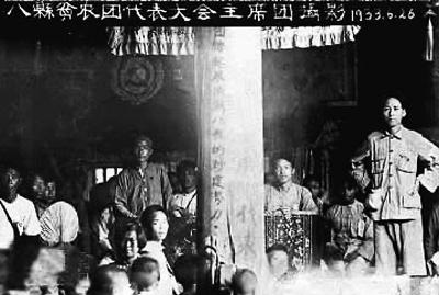 1933年6月25日至7月1日,临时中央政府在瑞金叶坪召开瑞金、会昌、胜利、于都、博生、石城、宁化、长汀等8县贫农团代表大会。毛泽东在会上作了查田运动的报告。图为中央苏区八县贫农团代表大会主席团合影。右一为毛泽东