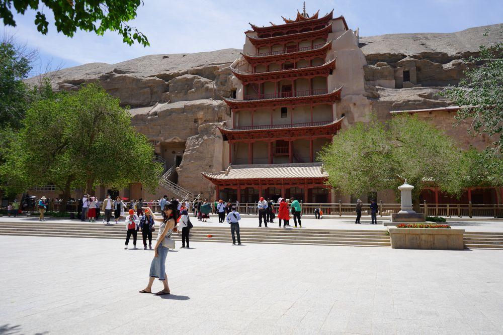 5月31日,游客在敦煌莫高窟游览、拍照。新华社记者郎兵兵 摄
