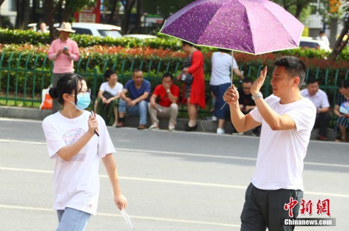 6月8日上午,家长将考生送抵江西省南昌市第十九中学考点后挥手暂别。 中新社记者 刘占昆 摄