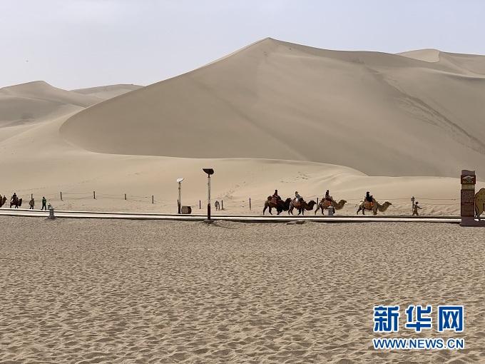 敦煌鸣沙山月牙泉景区内,游客骑着骆驼感受沙漠之美。新华社记者 李杰 摄