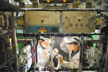 高莹莹(左)、胡莹琦在狭小的空间内配合完成插头焊接