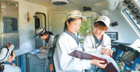 余欢欢(右)、薛丽娟在SS7E机车司机室操纵台对照连接线路