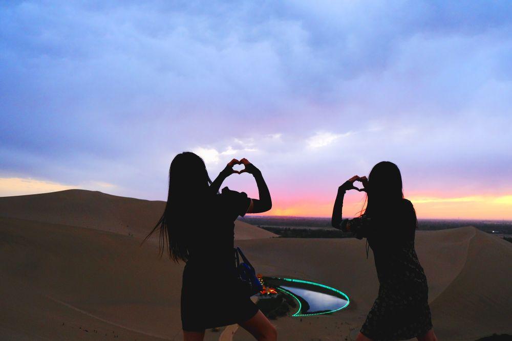 杨怡(左一)和朋友在鸣沙山月牙泉景区游览、拍照(受访者供图)