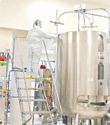 鼎康(武汉)生物医药有限企业,身着安全服的工作人员在无菌生产间里的生物安全柜和生物反应器等设备前有条不紊地忙碌着。