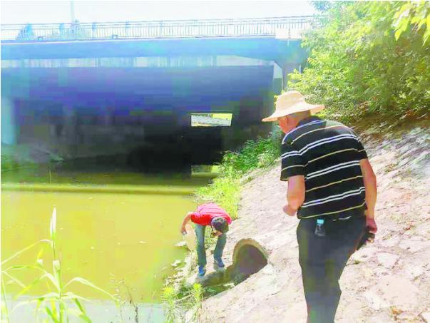 水务工作者烈日下巡视堤坝。