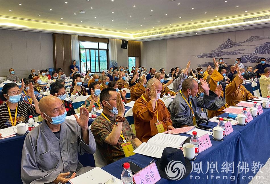 选举现场,举手通过。(图片来源:凤凰网佛教)