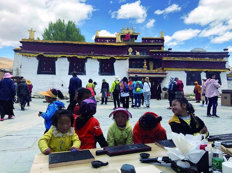 5月25日,四川理塘县勒通古镇工作人员在景区内举办藏式木版印刷的体验活动,住在古镇里的藏族小朋友中午放学后来围观活动。新京报记者 韩沁珂 摄