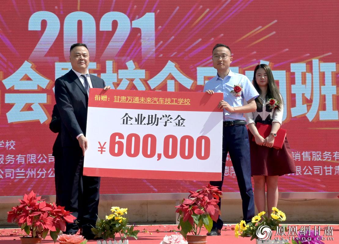 甘肃泓通汽车服务有限公司副总经理曹熤(前右)代表所在企业,向甘肃万通技工学校捐赠助学金。肖刚 摄